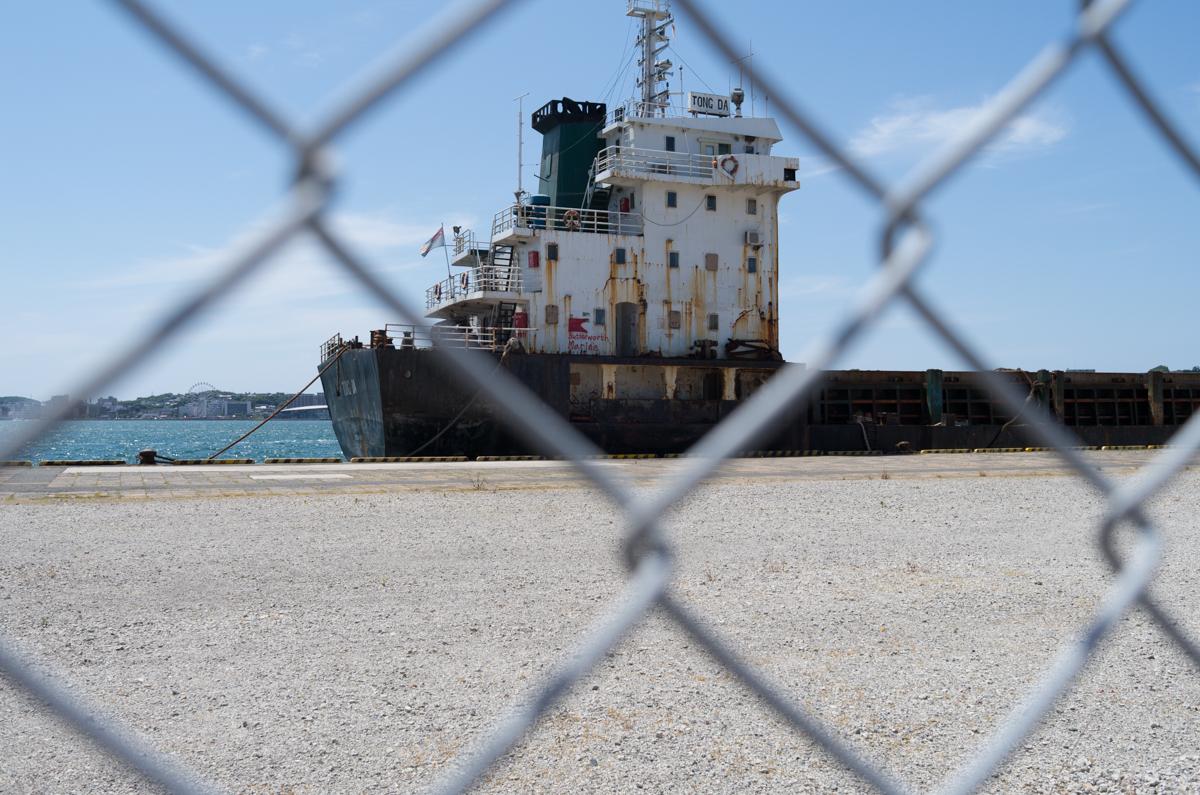 金網越しに錆びついた船を